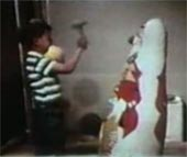 A child in the Bandura study, imitating the 'aggressive model' and proceeding to hit the Bobo doll with a mallet.